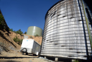 Shelter Cover water storage tank replacement. Old tank in foreground and new tank in background.