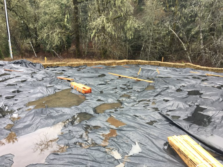 Contaminated soil is covered by tarps.